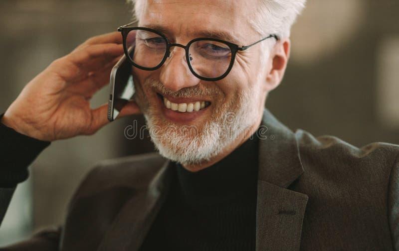Hombre de negocios maduro feliz que habla en el teléfono imágenes de archivo libres de regalías