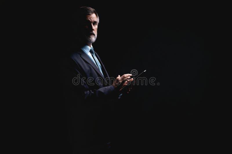 Hombre de negocios maduro feliz que trabaja con la tableta moderna aislada en fondo negro imagenes de archivo
