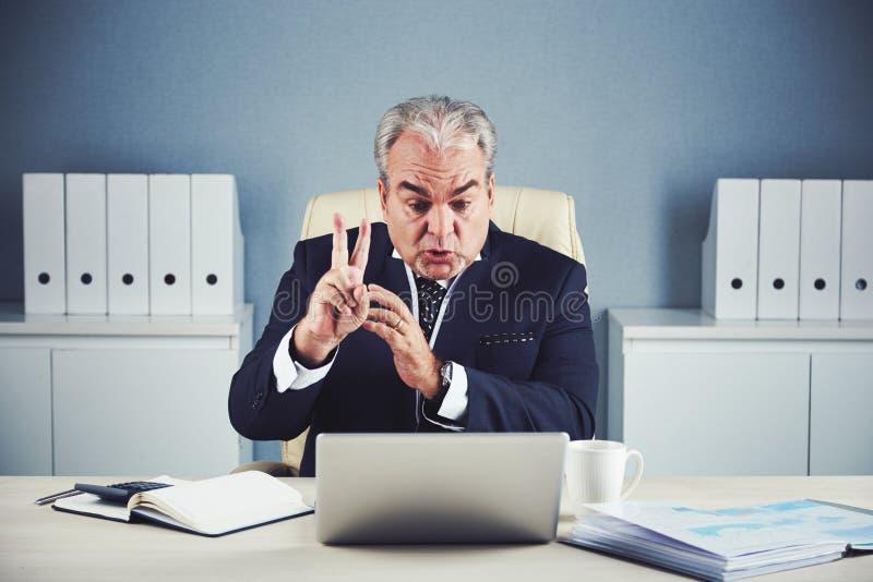 Hombre de negocios maduro furioso que habla en la charla video fotografía de archivo