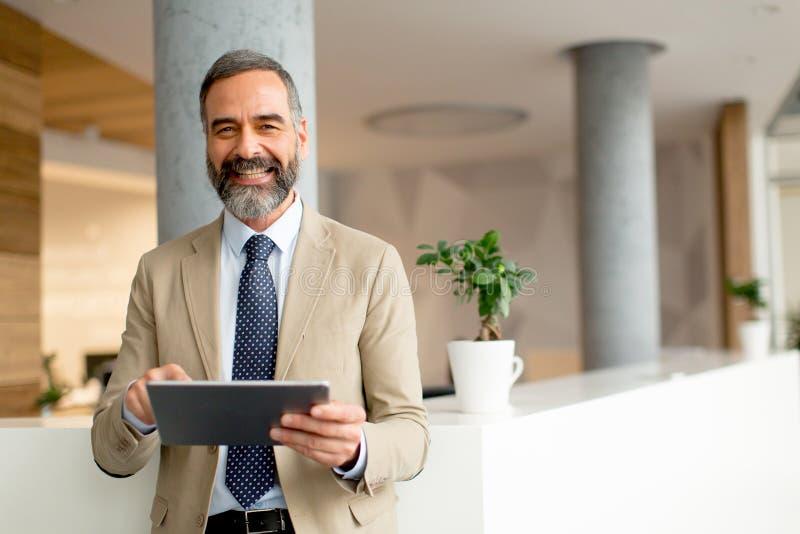 Hombre de negocios maduro hermoso con la tableta digital en la oficina foto de archivo