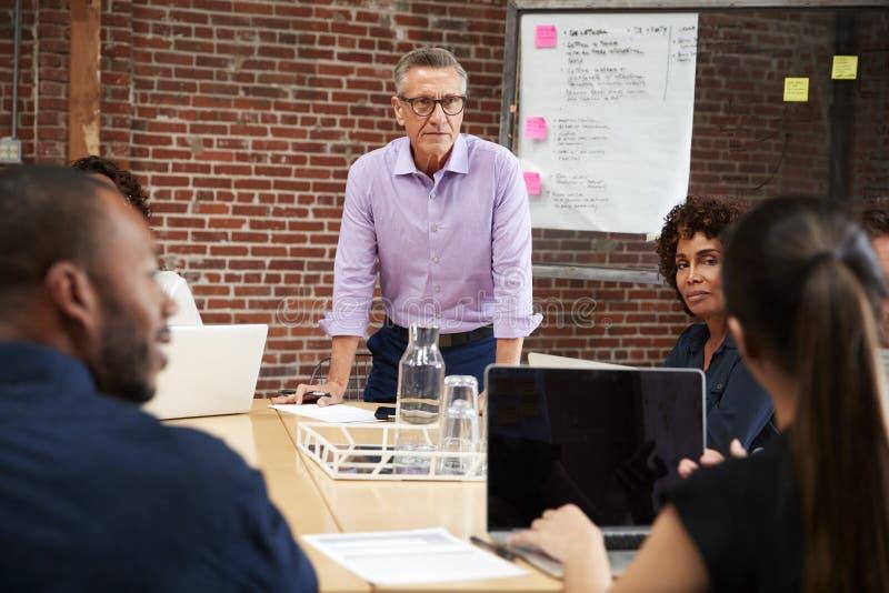 Hombre de negocios maduro Leading Office Meeting de los colegas que se sientan alrededor de la tabla fotos de archivo
