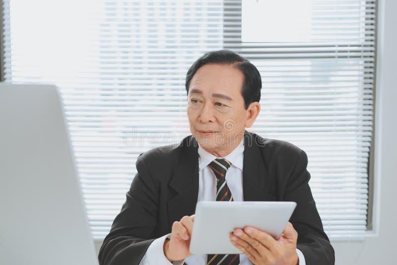 Hombre de negocios maduro mayor que se sienta en la oficina delante del ordenador port?til y que sostiene una tableta digital imagen de archivo libre de regalías