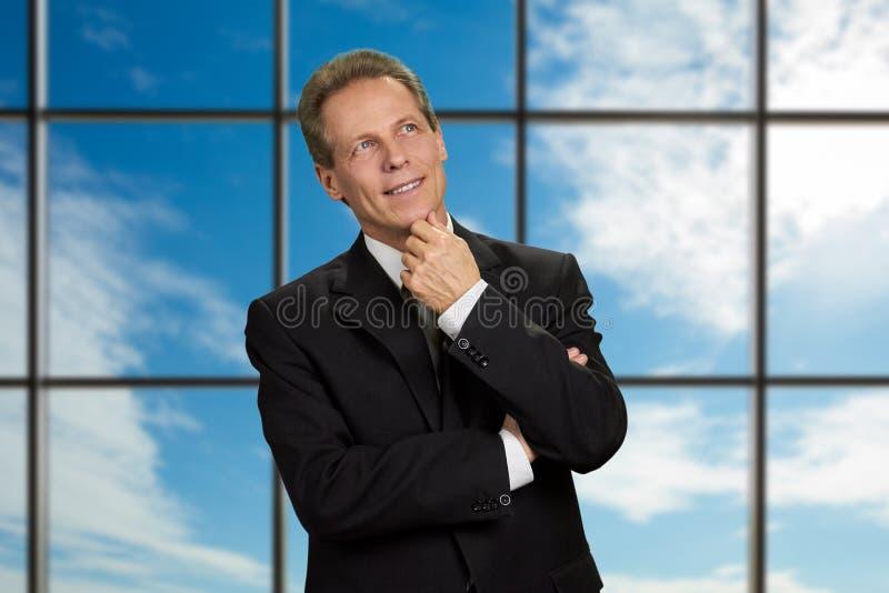 Hombre de negocios maduro de pensamiento en fondo del cielo imagenes de archivo