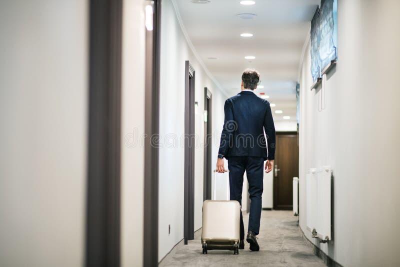 Hombre de negocios maduro que camina con equipaje en un pasillo del hotel imágenes de archivo libres de regalías