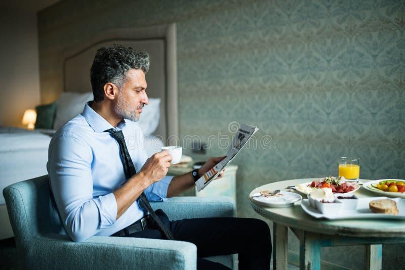 Hombre de negocios maduro que desayuna en una habitación imágenes de archivo libres de regalías