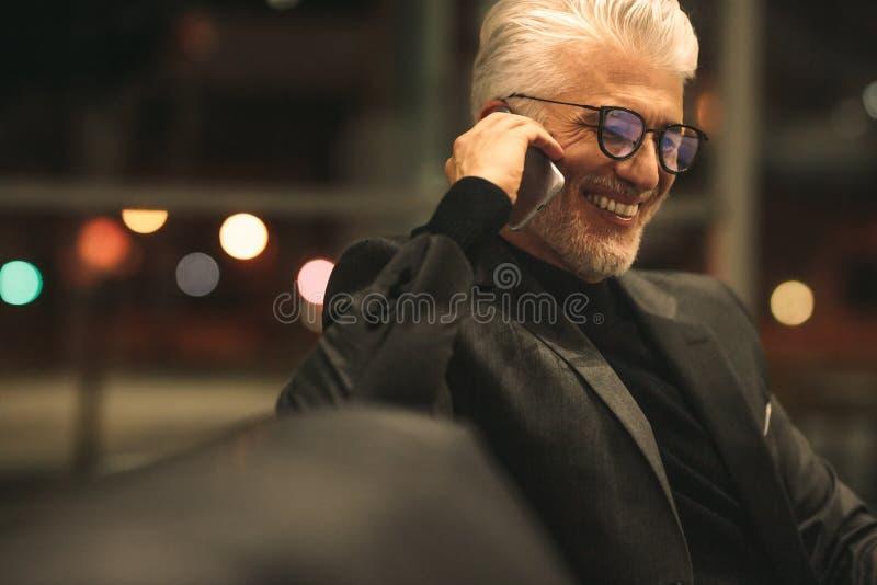 Hombre de negocios maduro que habla en el teléfono móvil en oficina fotografía de archivo