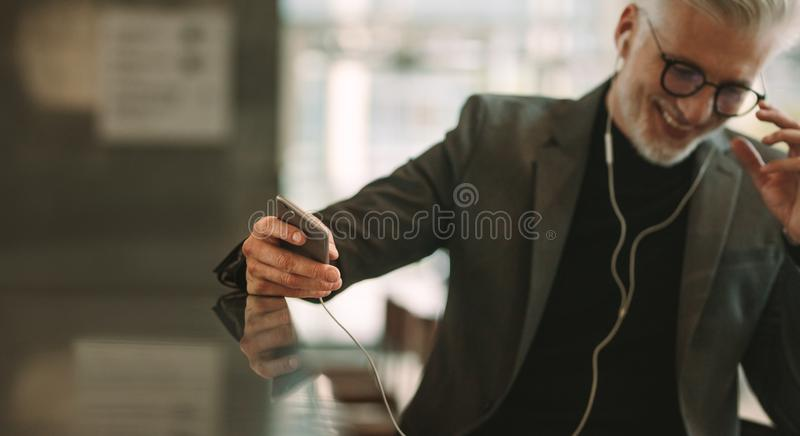 Hombre de negocios maduro que se sienta en el café con el teléfono imágenes de archivo libres de regalías
