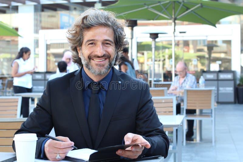 Hombre de negocios maduro que trabaja en la sonrisa del café del aire libre fotografía de archivo