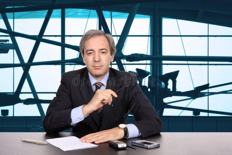 Hombre de negocios maduro que trabaja en su escritorio imagen de archivo