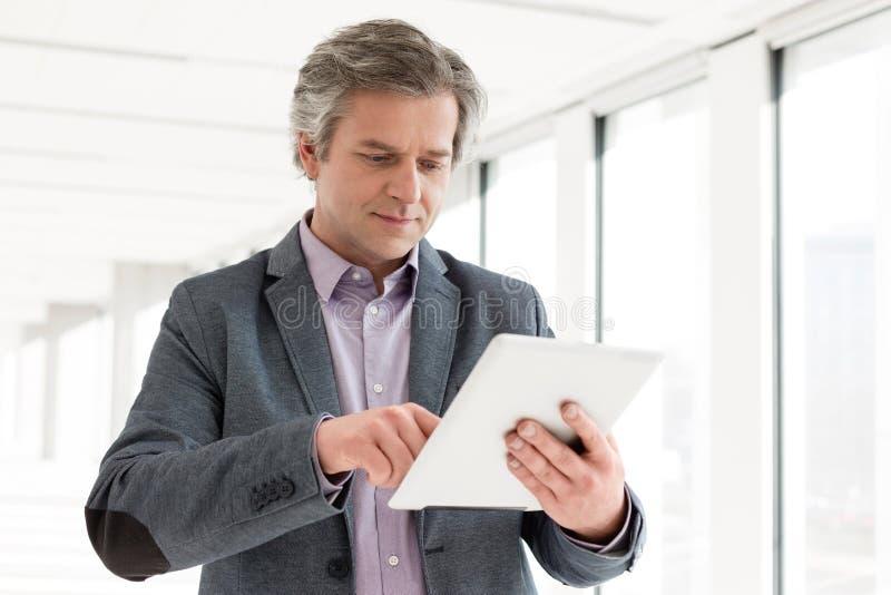 Hombre de negocios maduro usando la tableta digital en nueva oficina fotos de archivo libres de regalías