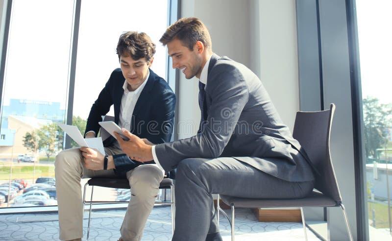 Hombre de negocios maduro usando una tableta digital para discutir la información con un colega más joven en una oficina de negoc imagenes de archivo