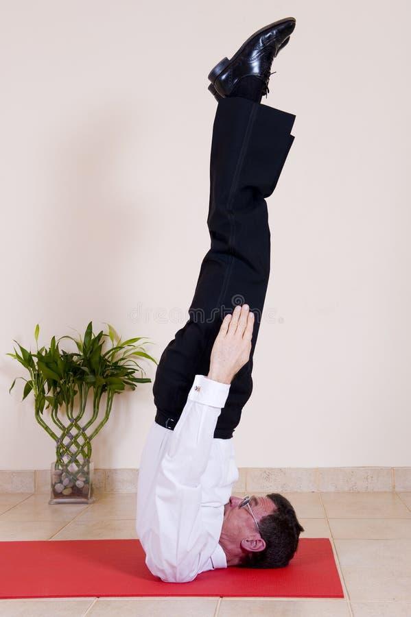 Hombre de negocios maduros atractivo que hace yoga foto de archivo