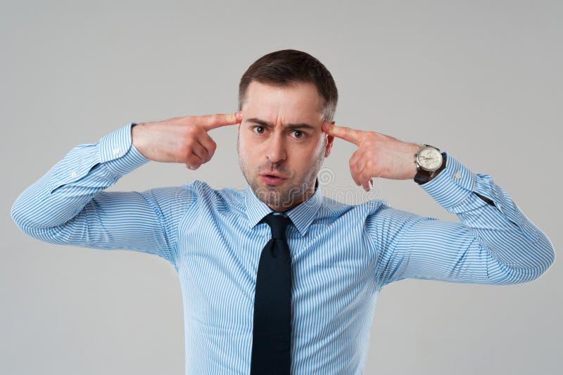Hombre de negocios maduros con los fingeres en la cabeza foto de archivo