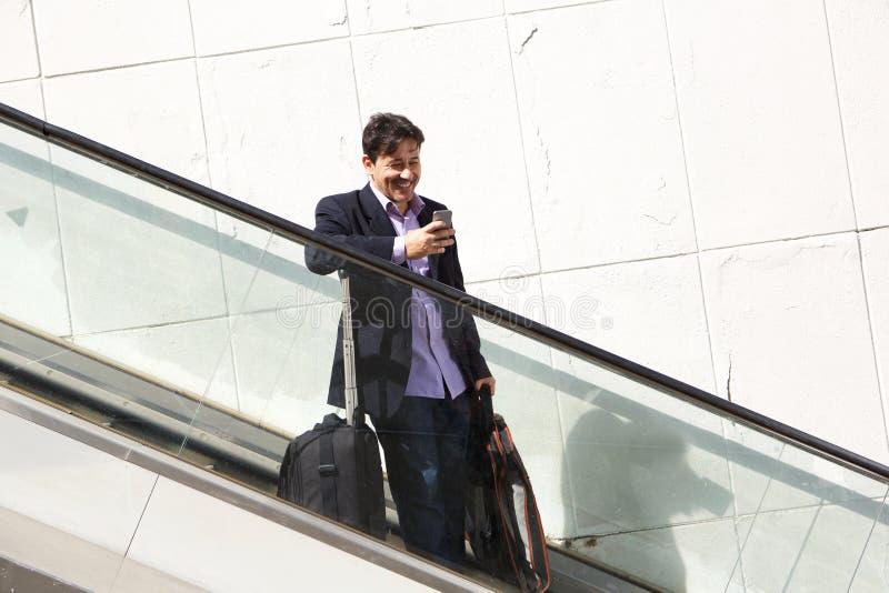 Hombre de negocios maduros hermoso en la escalera móvil usando el teléfono móvil fotografía de archivo libre de regalías