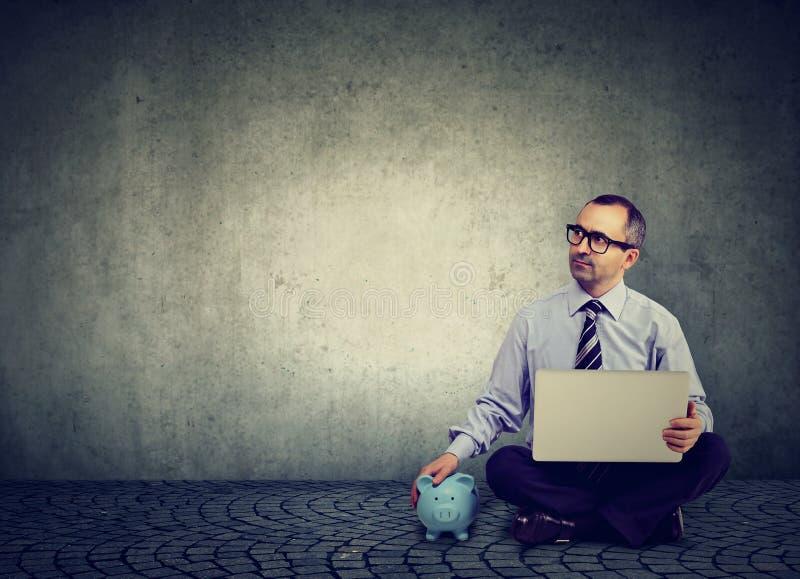 Hombre de negocios maduros pensativo con el ordenador portátil y la hucha que se sientan en un piso fotos de archivo