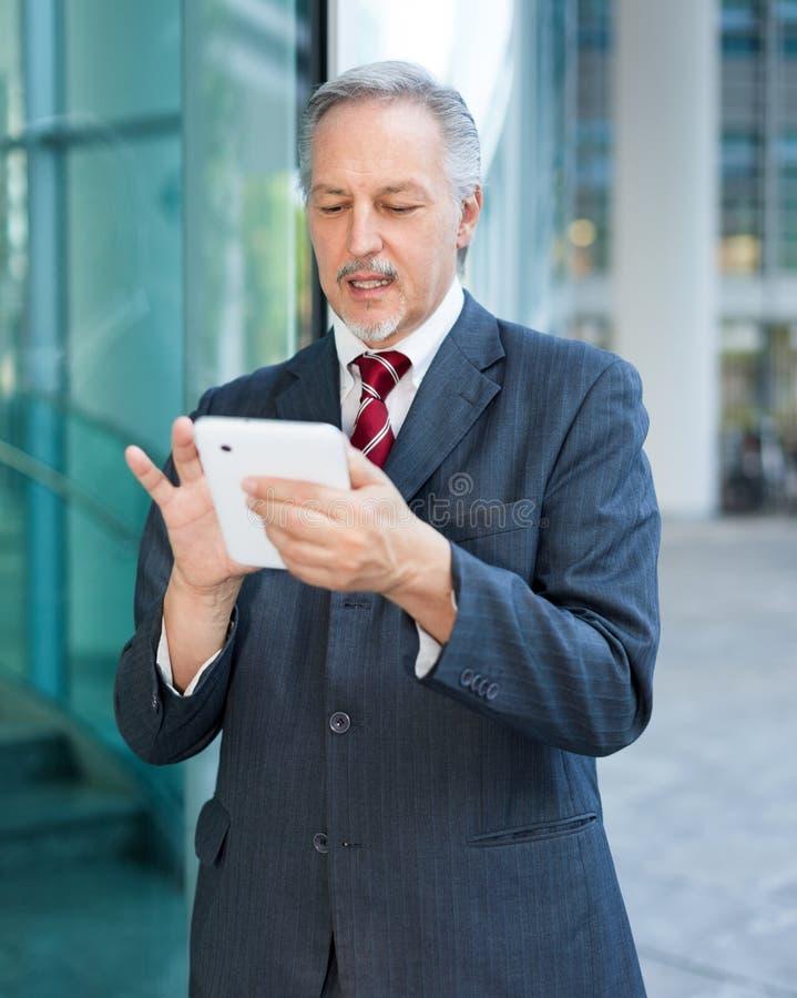 Hombre de negocios maduros que usa una tableta foto de archivo libre de regalías