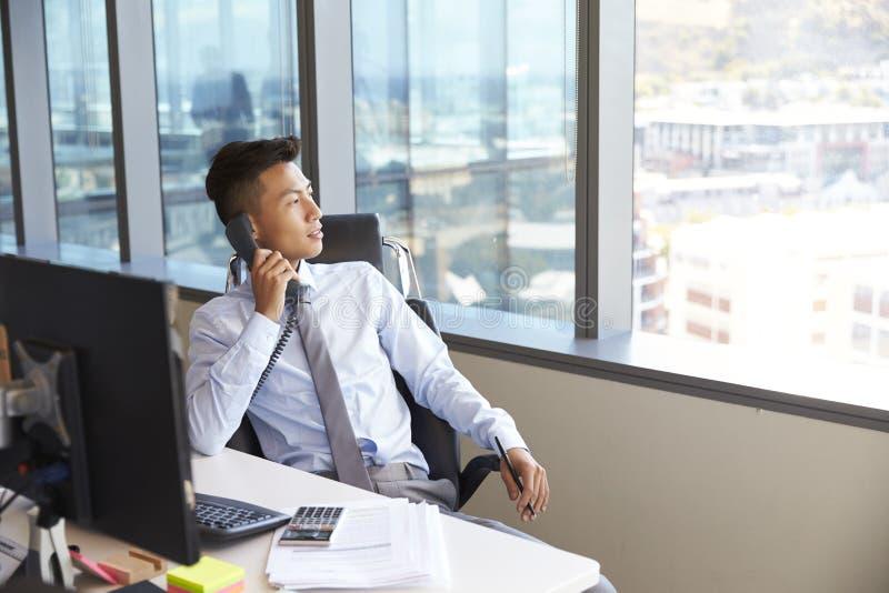 Hombre de negocios Making Phone Call que se sienta en el escritorio en oficina fotos de archivo