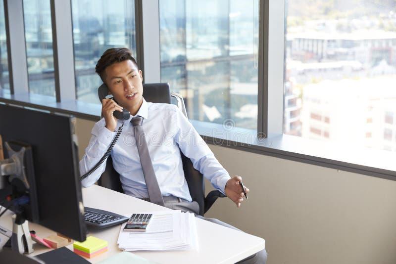 Hombre de negocios Making Phone Call que se sienta en el escritorio en oficina foto de archivo
