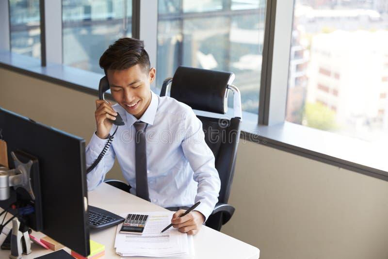 Hombre de negocios Making Phone Call que se sienta en el escritorio en oficina imagen de archivo