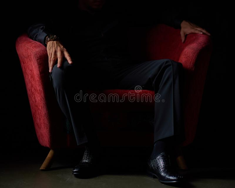 Hombre de negocios masculino en un traje negro que se sienta en la silla roja, fondo negro, ningunas caras visibles, tiroteo del  imagenes de archivo