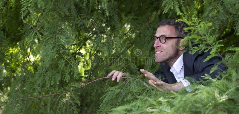 Hombre de negocios masculino fóbico que oculta para las soluciones estratégicas de la dirección al aire libre fotografía de archivo libre de regalías