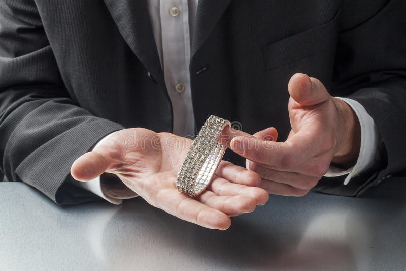 Hombre de negocios masculino que comprueba una pulsera para saber si hay ofrecer un regalo fotos de archivo libres de regalías