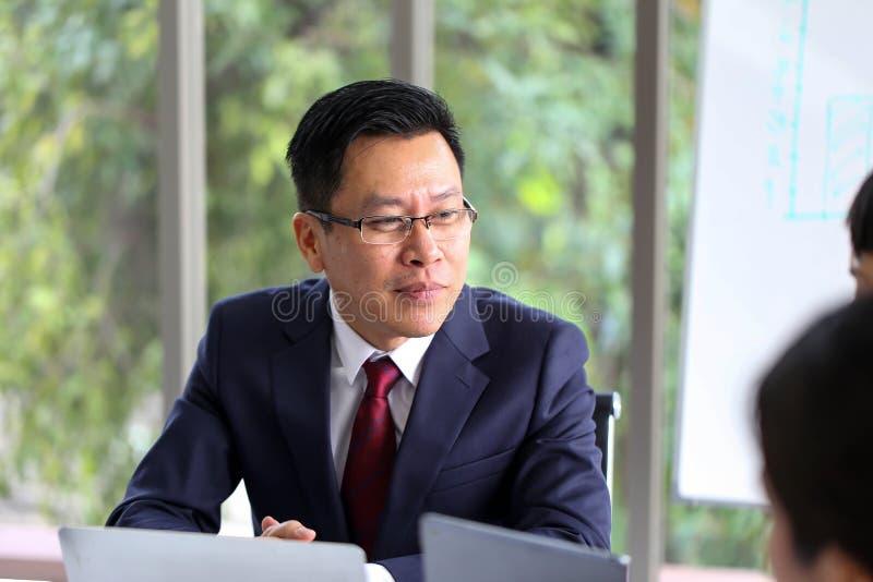 Hombre de negocios mayor Asia con la discusión de la reunión de unidad de negocio fotografía de archivo libre de regalías
