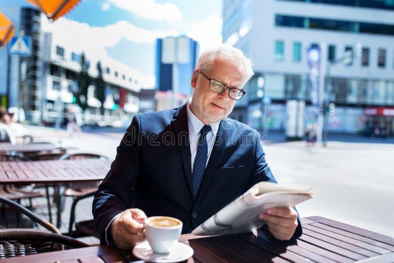 Hombre de negocios mayor con café de consumición del periódico fotografía de archivo
