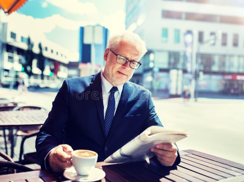 Hombre de negocios mayor con caf? de consumici?n del peri?dico imagenes de archivo