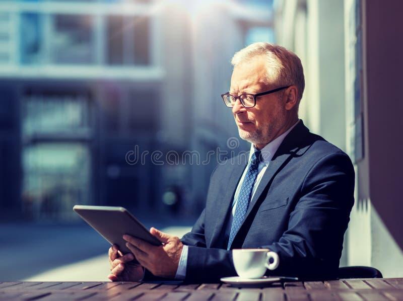 Hombre de negocios mayor con caf? de consumici?n de la PC de la tableta fotos de archivo