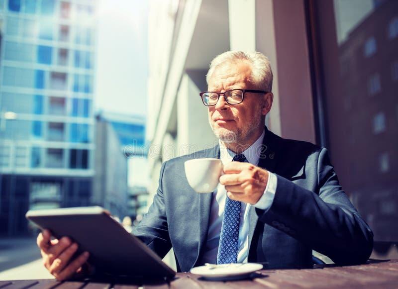 Hombre de negocios mayor con caf? de consumici?n de la PC de la tableta fotografía de archivo