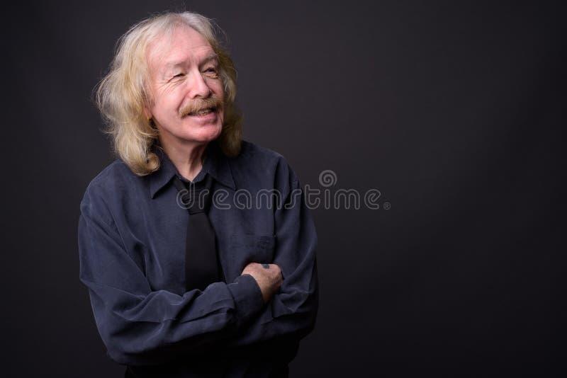 Hombre de negocios mayor con el bigote contra fondo gris imágenes de archivo libres de regalías