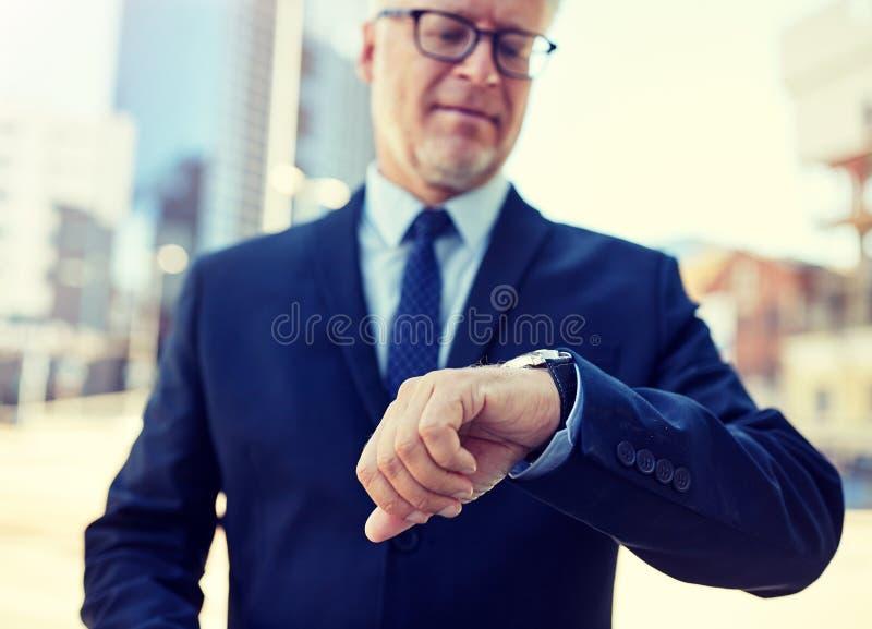Hombre de negocios mayor con el reloj en la calle de la ciudad imagen de archivo libre de regalías