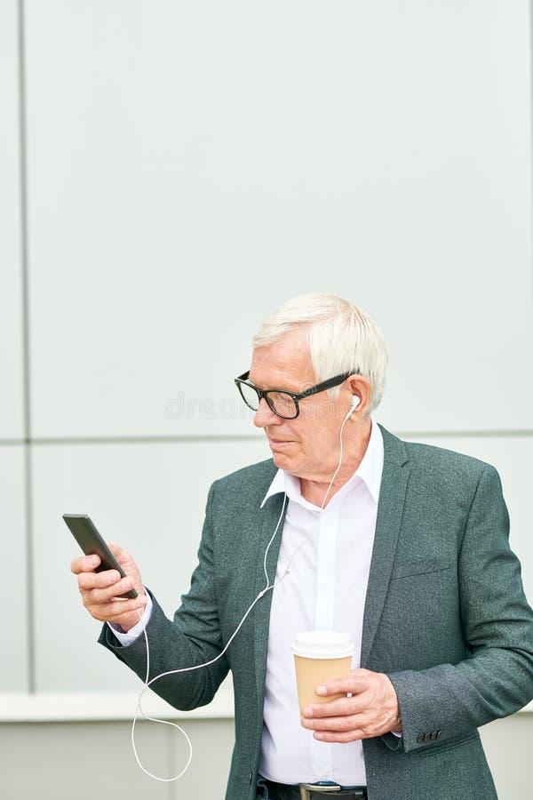 Hombre de negocios mayor con la bebida que escucha la música fotos de archivo