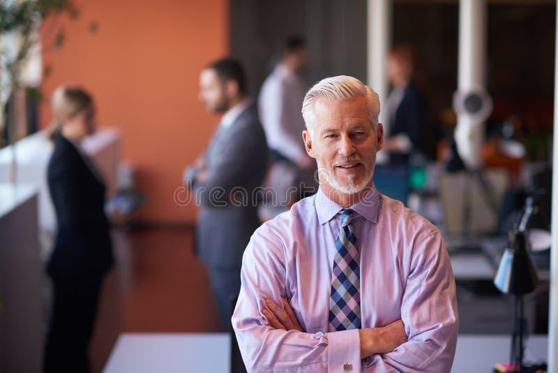 Hombre de negocios mayor con su equipo en la oficina fotografía de archivo