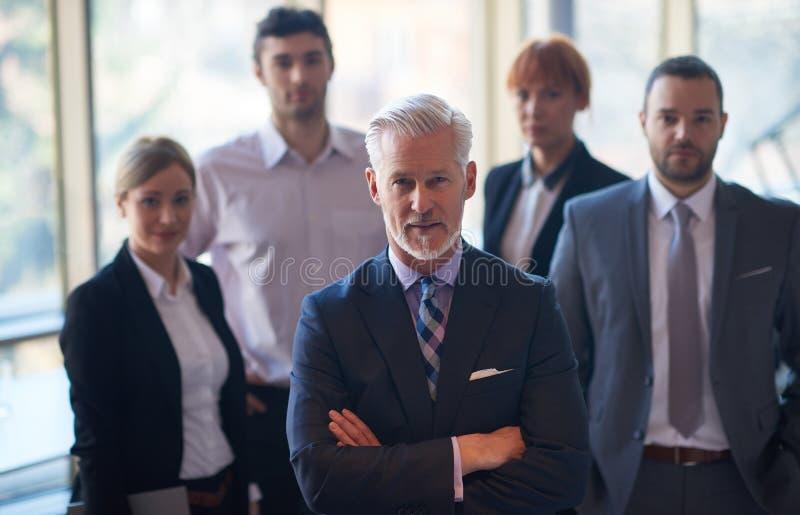 Hombre de negocios mayor con su equipo en la oficina fotos de archivo