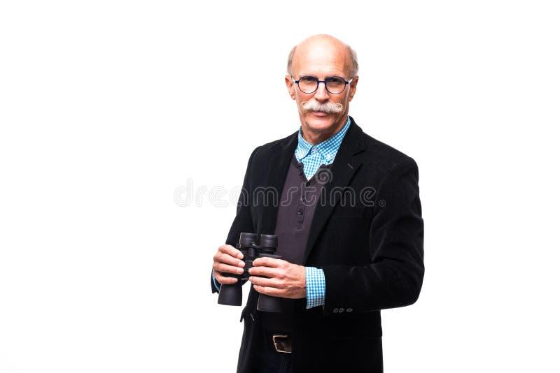 Hombre de negocios mayor en el traje que mira a través de los prismáticos en el fondo blanco fotos de archivo libres de regalías