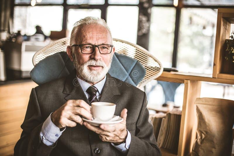 Hombre de negocios mayor en su sentada de la oficina, café de consumición foto de archivo libre de regalías