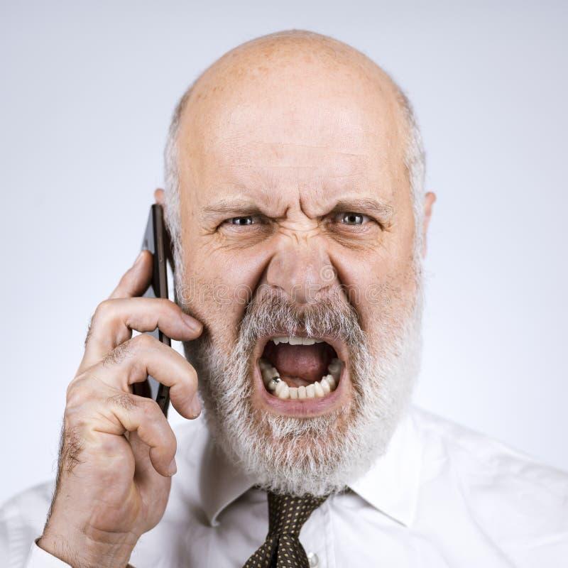 Hombre de negocios mayor enojado que tiene una llamada de teléfono foto de archivo