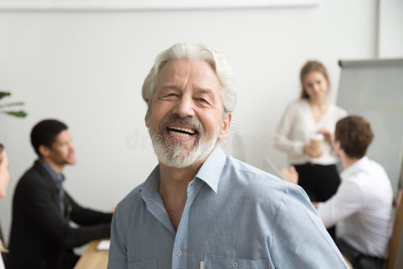 Hombre de negocios mayor feliz que ríe mirando la cámara en la oficina, p imagenes de archivo