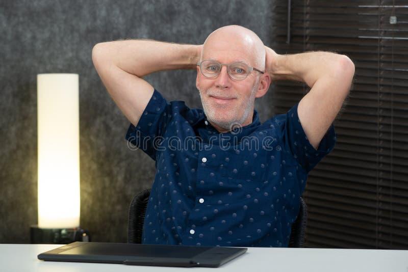 Hombre de negocios mayor hermoso que se relaja en la oficina fotos de archivo libres de regalías
