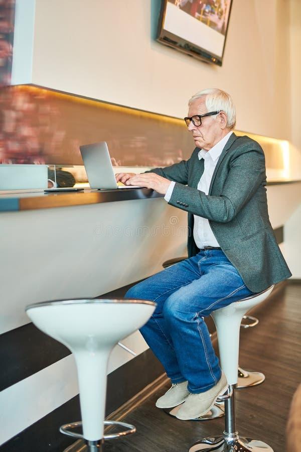 Hombre de negocios mayor moderno Using Laptop en barra foto de archivo
