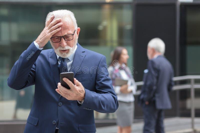 Hombre de negocios mayor preocupante que recibe malas noticias de los socios comerciales, llevando a cabo su cabeza foto de archivo libre de regalías