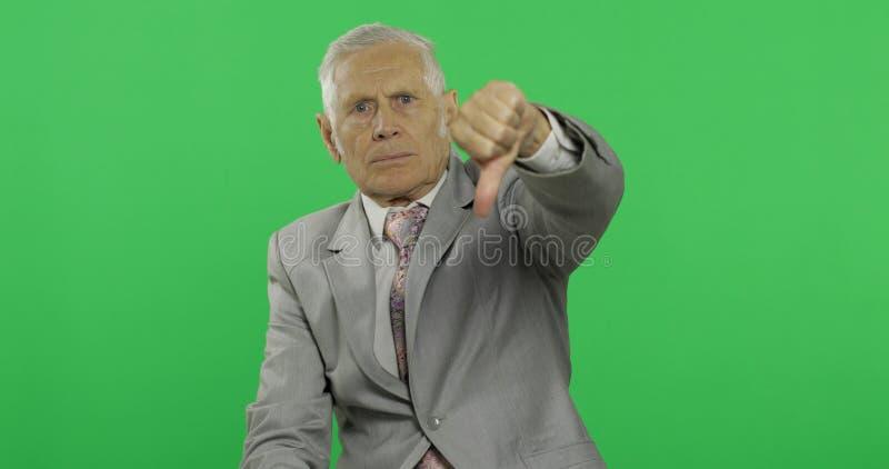 Hombre de negocios mayor que da el pulgar dow Viejo hombre en pulgar de la demostración del desgaste formal abajo fotos de archivo