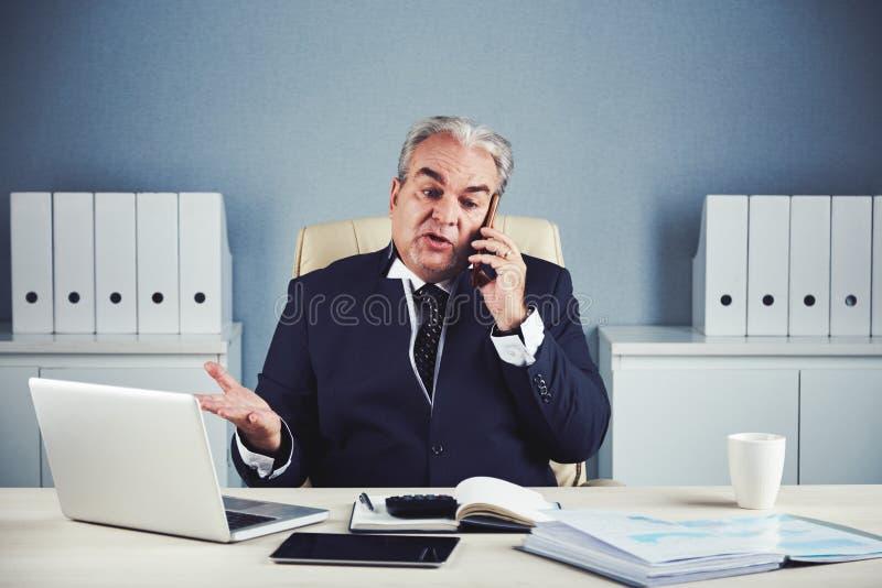 Hombre de negocios mayor que explica algo que habla en smartphone fotos de archivo libres de regalías