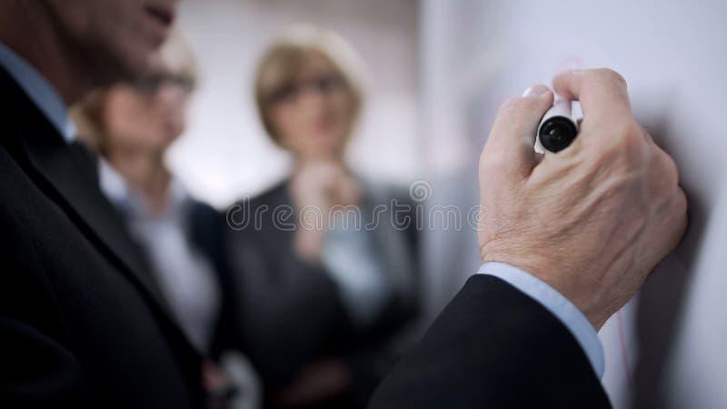 Hombre de negocios mayor que habla con colegas más jovenes y que escribe a bordo, planeando fotografía de archivo
