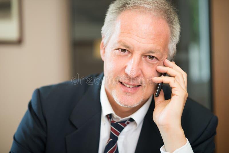 Hombre de negocios mayor que habla en el teléfono en su oficina fotos de archivo libres de regalías
