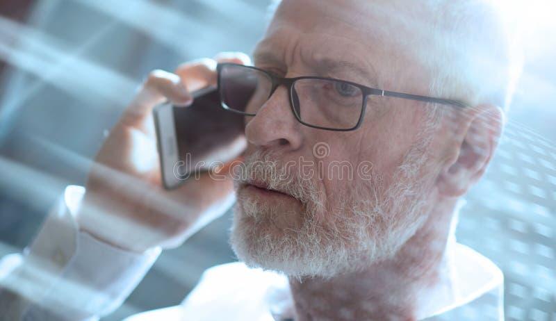 Hombre de negocios mayor que habla en el teléfono móvil, efecto luminoso; multip imagen de archivo