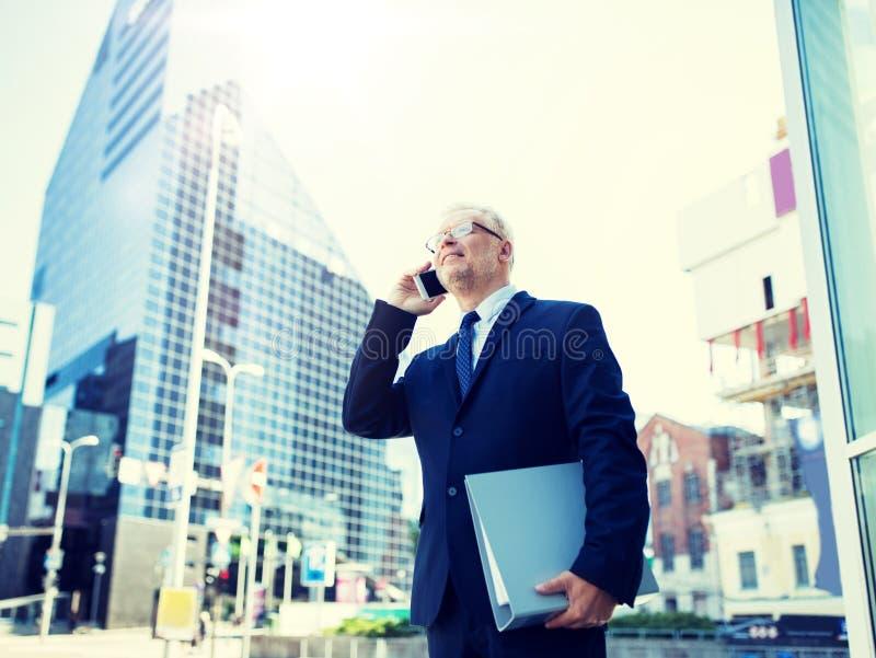 Hombre de negocios mayor que invita a smartphone en ciudad foto de archivo