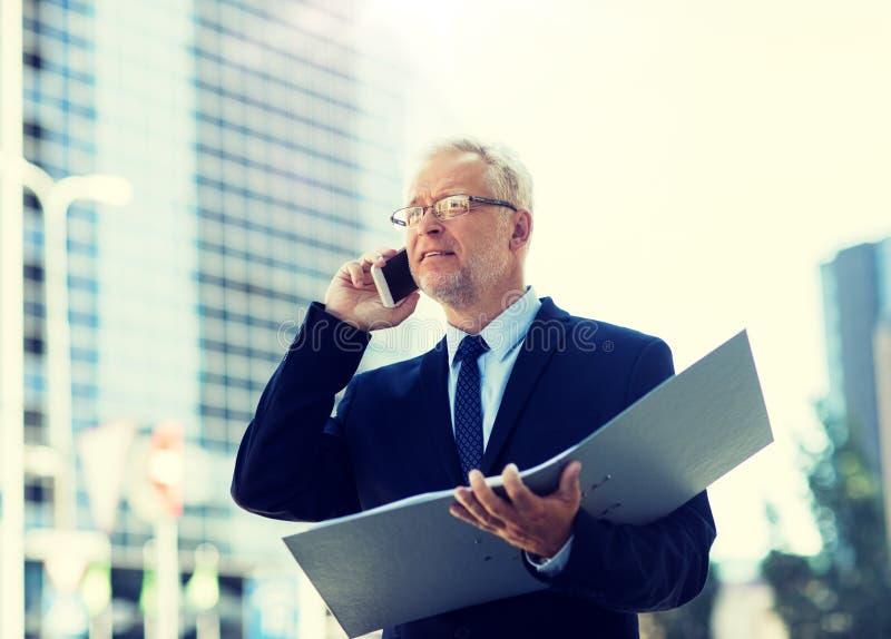 Hombre de negocios mayor que invita a smartphone en ciudad imagenes de archivo
